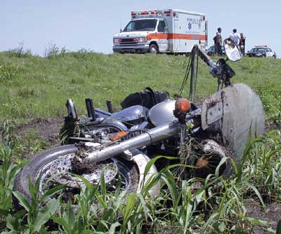 Photo by Matt Swearengin, Durant Democrat --- Motorcycle accident 2 miles west of Caddo on State Hwy. 22. Patient was taken by Lifestar 1, to TMC. --- Caney VFD and Bryan County EMS worked to stabilized patient before helicopter arrived. 5-18-02
