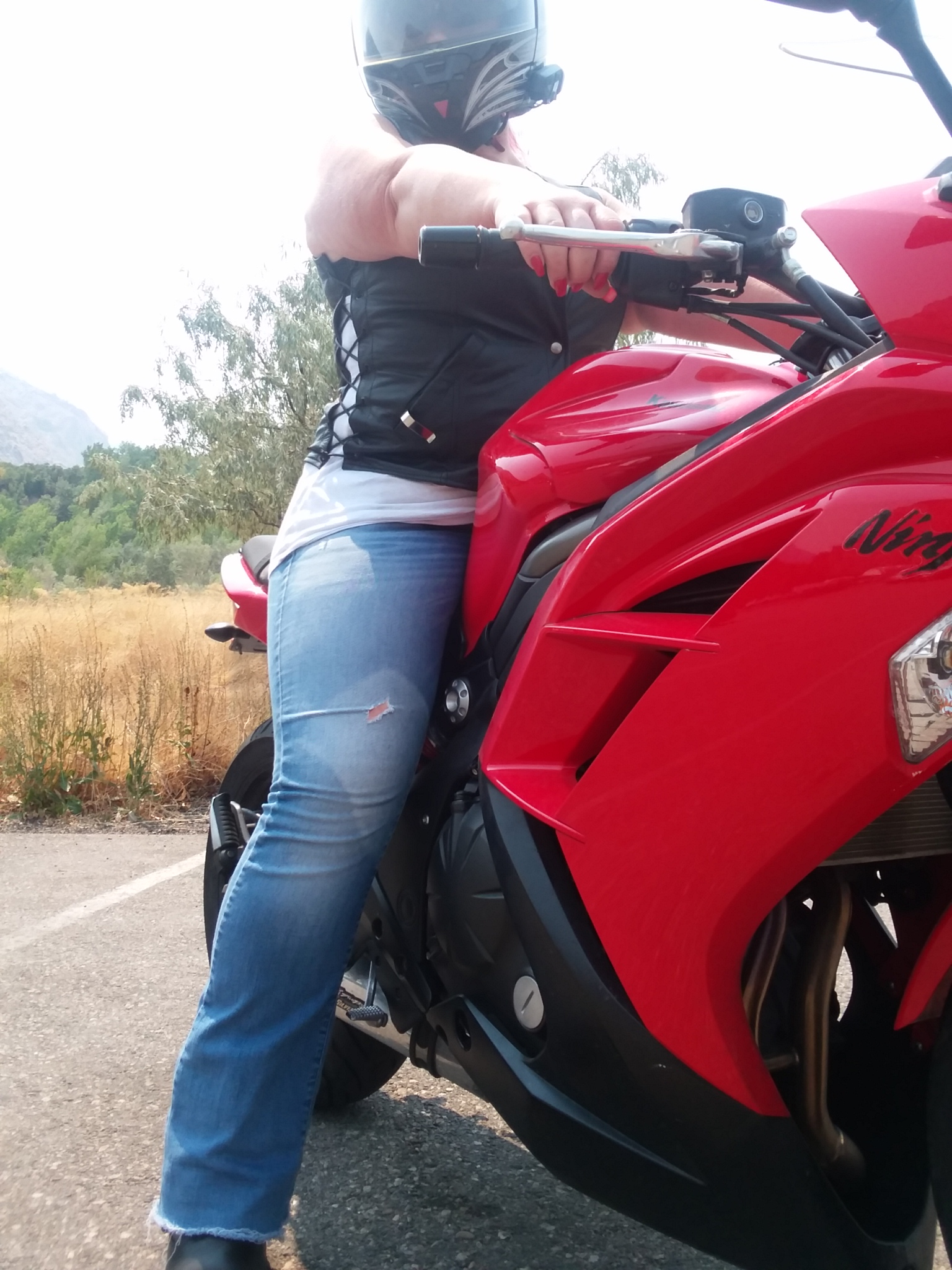 A helmeted woman sits astride a red Kawasaki Ninja 650, looking down at the camera, which faces up from a low vantage. She wears blue jeans, a white tank top and black leather vest. The tank top is visible through laces in the side of the vest. Her right arm is extended and she clutches the throttle of the motorcycle, showing brightly manicured red fingernails.