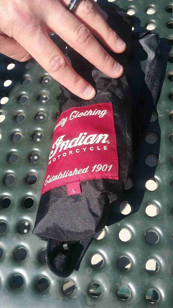 The liner of the Shadow Mesh Jacket is pictured, rolled up tightly to roughly the size of an emergency poncho. A bright red patch bearing the Indian Logo is prominently visible.