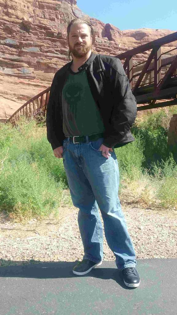A man stands casually in a desert scene, wearing the Shadow Mesh Jacket from Indian Motorcycle. Behind him, a steel bridge spans a wide river basin.