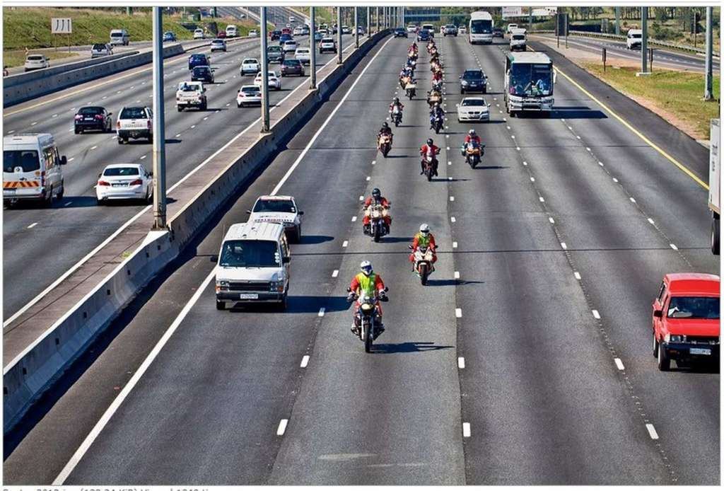 22 Motorcycle riders dressed like Santa Clause wearing helmets ride in staggered formation on a 5 lane freeway