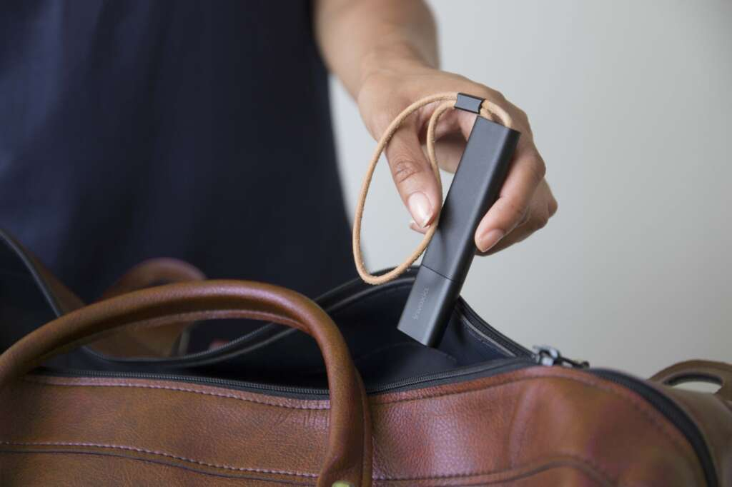 Pictured is an unidentified person, only their hand visible, holding the Invoxia GPS Tracker and placing it inside a brown leather handbag.